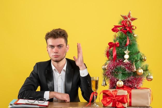 Vooraanzicht mannelijke werknemer achter zijn werkplek met cadeautjes zijn hand opheffen op geel