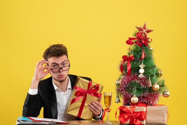 Vooraanzicht mannelijke werknemer achter zijn werkplek met verschillende cadeautjes op geel