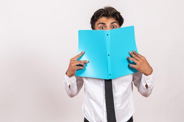 Vooraanzicht mannelijke werknemer die documenten controleert op witte bureau mannelijke zakelijke werkbaan
