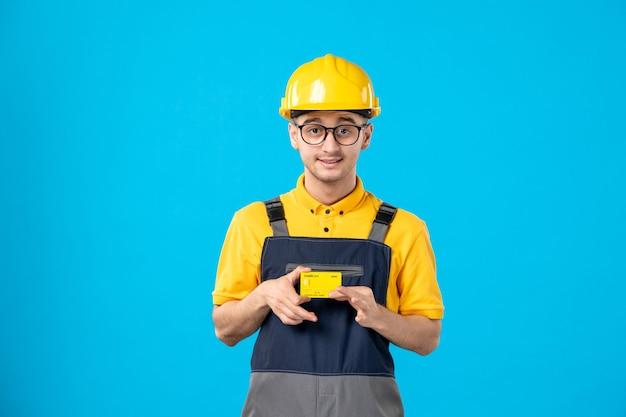 Vooraanzicht mannelijke werknemer in geel uniform met creditcard op een blauw