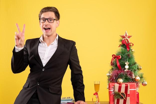 Vooraanzicht mannelijke werknemer in pak staande rond cadeautjes en kerstboom