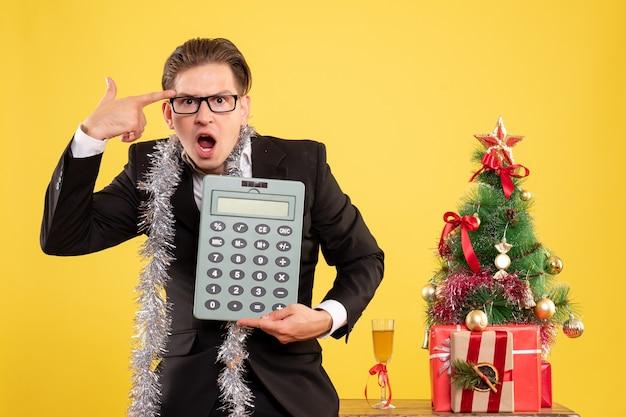 Vooraanzicht mannelijke werknemer in pak staande te houden rekenmachine