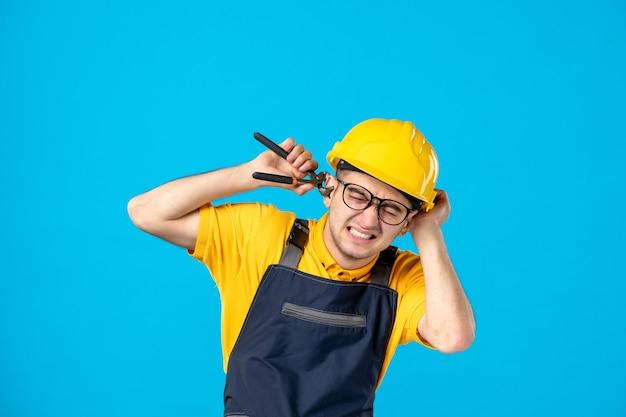Vooraanzicht mannelijke werknemer in uniform en helm die zijn oor op blauw snijdt