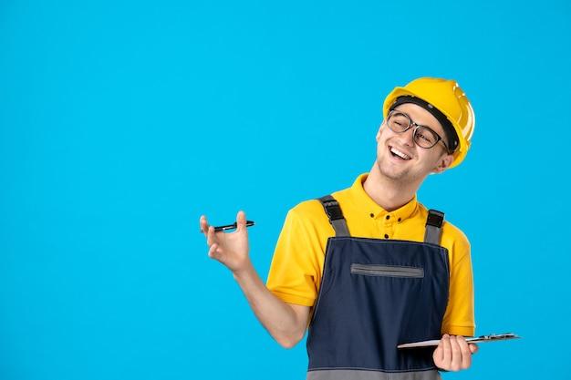 Vooraanzicht mannelijke werknemer in uniform en helm notities maken en lachen op blauw