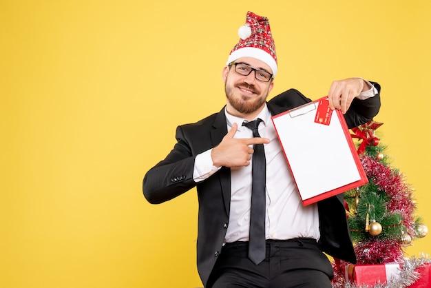 Vooraanzicht mannelijke werknemer met bankbiljetten en bankkaart op geel