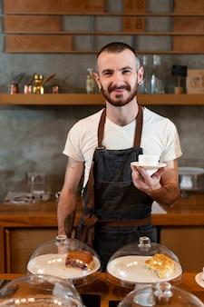 Vooraanzicht mannelijke werknemer serveert koffie