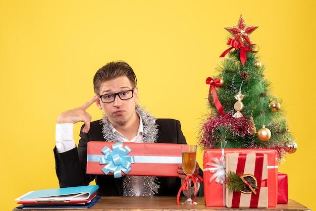 Vooraanzicht mannelijke werknemer zitten en houden kerstcadeau