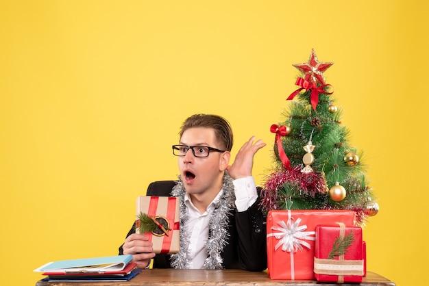 Vooraanzicht mannelijke werknemer zitten met cadeautjes