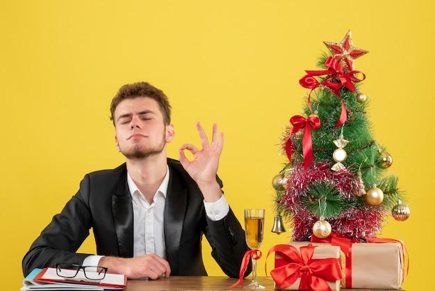 Vooraanzicht mannelijke werknemer zittend achter zijn werkplek op een geel