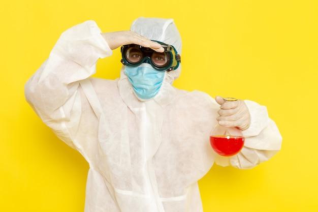 Vooraanzicht mannelijke wetenschappelijke werker in speciaal beschermend pak bedrijf kolf met rode oplossing op geel oppervlak
