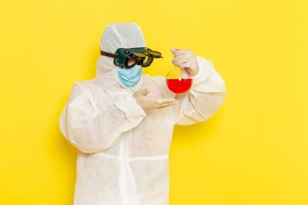 Vooraanzicht mannelijke wetenschappelijke werker in speciaal beschermend pak met kolf met rode oplossing op geel bureau