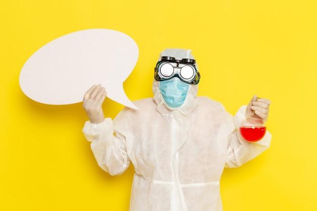 Vooraanzicht mannelijke wetenschappelijke werker in speciale beschermende pak houden kolf met rode oplossing en wit bord op geel bureau