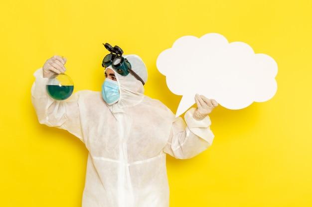 Vooraanzicht mannelijke wetenschappelijke werker in speciale pak met kolf met groene oplossing en groot wit bord op geel bureau