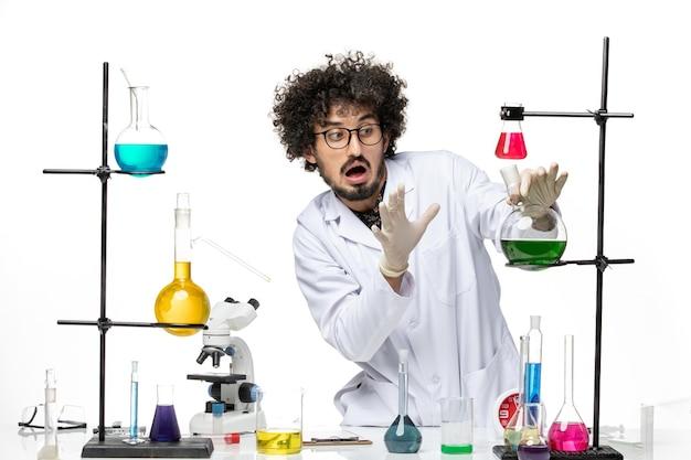 Vooraanzicht mannelijke wetenschapper in de oplossing van de medische pakholding op witte ruimte