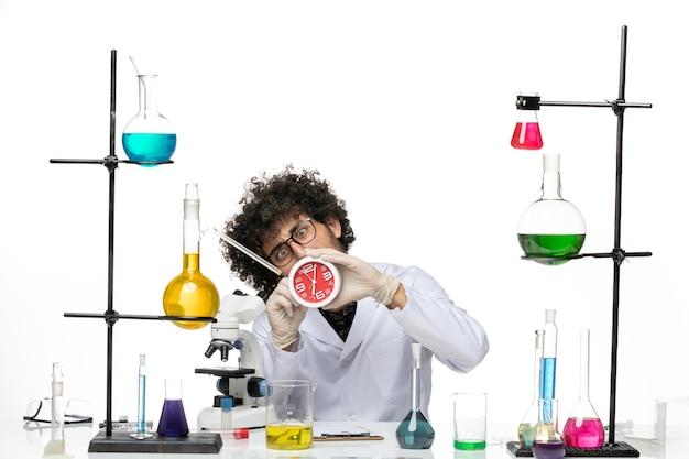 Vooraanzicht mannelijke wetenschapper in medisch pak met rode klokken op de lichte witte ruimte