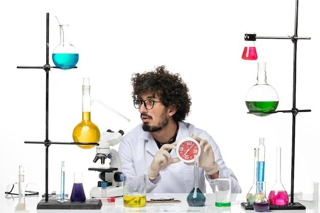 Vooraanzicht mannelijke wetenschapper in medisch pak met rode klokken op licht-witte vloer covid-lab wetenschap chemie virus
