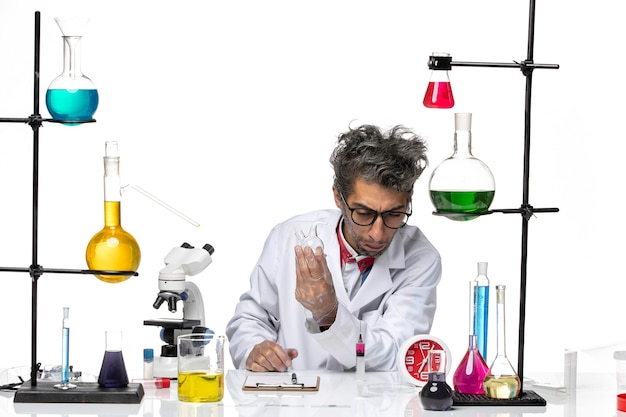 Vooraanzicht mannelijke wetenschapper in medisch pak werken met kolf