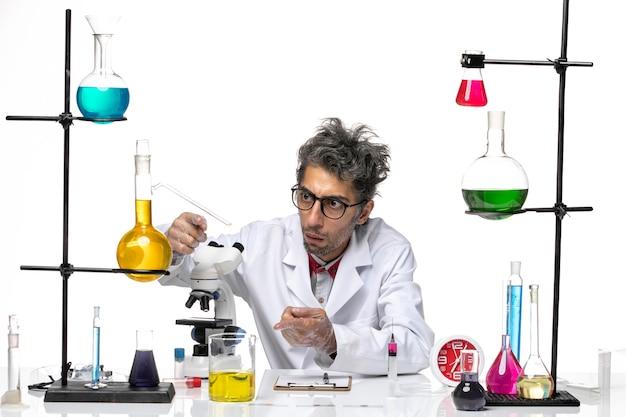 Vooraanzicht mannelijke wetenschapper in medisch pak werken met microscoop