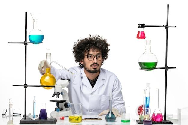 Vooraanzicht mannelijke wetenschapper in medisch pak werken met oplossingen op witte ruimte