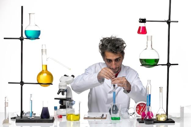 Vooraanzicht mannelijke wetenschapper in medisch pak werken met oplossingen