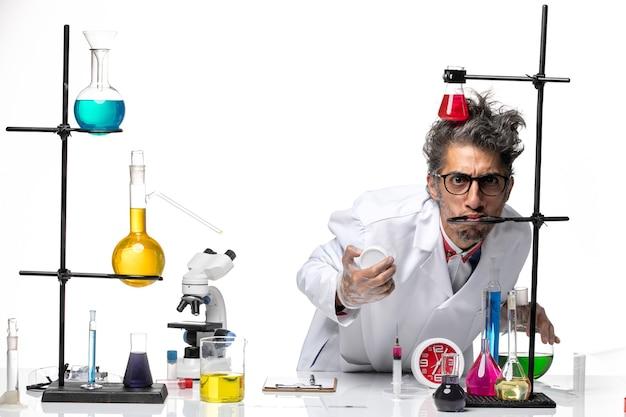 Vooraanzicht mannelijke wetenschapper in medisch pak werken met verschillende oplossingen grappige gezichten maken op witte achtergrond chemie covid lab virus