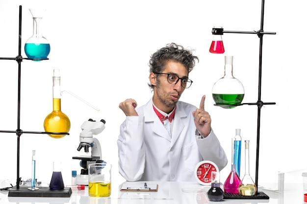 Vooraanzicht mannelijke wetenschapper in medisch pak zit tafel met oplossingen op de lichte witte achtergrond covid-lab virus gezondheid chemie