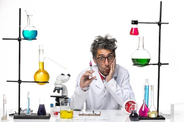 Vooraanzicht mannelijke wetenschapper in medische pak met injectie op het licht witte achtergrond chemie covid-lab virus