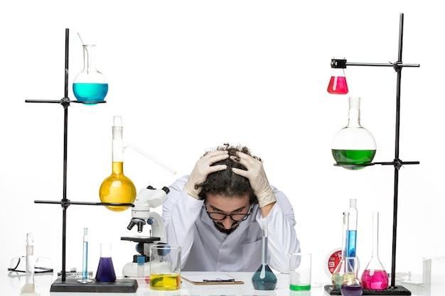 Vooraanzicht mannelijke wetenschapper in medische pak zitten en moe voelen op witte ruimte