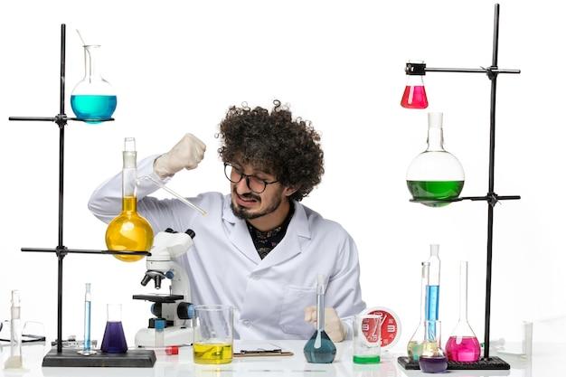 Vooraanzicht mannelijke wetenschapper in medische pak zittend met oplossingen en microscoop op lichte witte ruimte