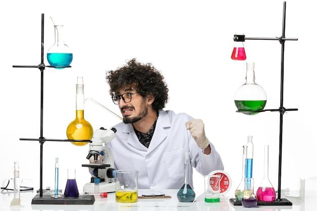 Vooraanzicht mannelijke wetenschapper in medische pak zittend met oplossingen en microscoop op witte ruimte