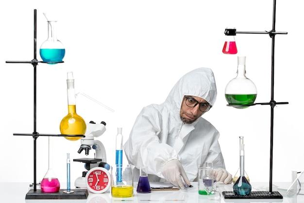 Vooraanzicht mannelijke wetenschapper in speciaal beschermend pak die met oplossingen werkt