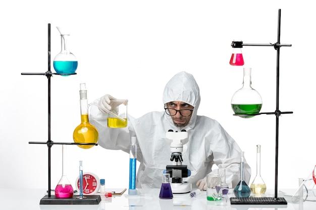 Vooraanzicht mannelijke wetenschapper in speciaal beschermend pak die microscoop probeert te bevestigen