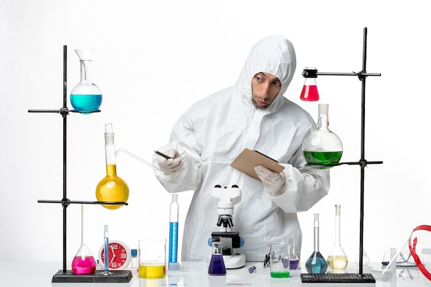 Vooraanzicht mannelijke wetenschapper in speciaal beschermend pak, het maken van aantekeningen