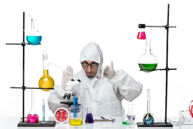 Vooraanzicht mannelijke wetenschapper in speciaal beschermend pak in werkproces