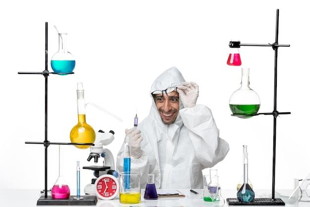 Vooraanzicht mannelijke wetenschapper in speciaal beschermend pak injectie houden en glimlachen