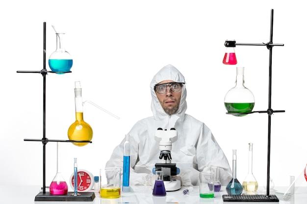 Vooraanzicht mannelijke wetenschapper in speciaal beschermend pak met behulp van microscoop