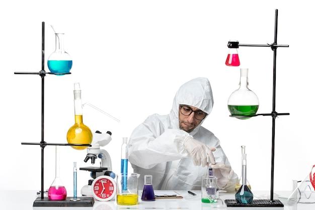 Vooraanzicht mannelijke wetenschapper in speciaal beschermend pak met injectie