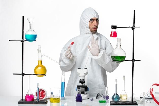 Vooraanzicht mannelijke wetenschapper in speciaal beschermend pak met kleine lege kolf