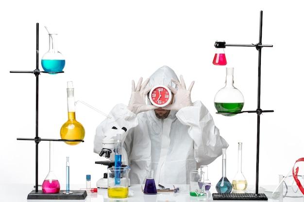 Vooraanzicht mannelijke wetenschapper in speciaal beschermend pak met klokken