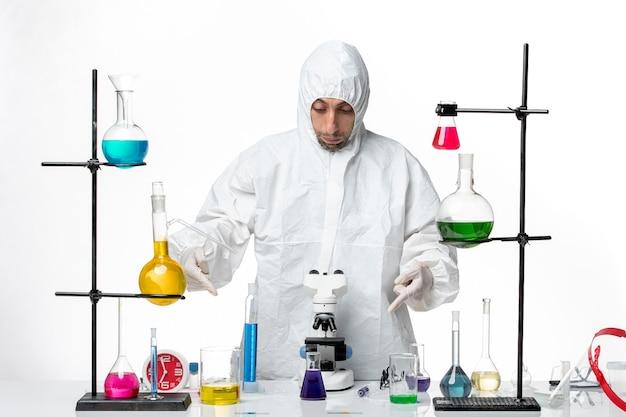Vooraanzicht mannelijke wetenschapper in speciaal beschermend pak staande rond tafel met oplossingen
