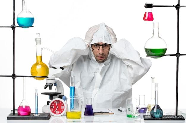 Vooraanzicht mannelijke wetenschapper in speciaal beschermend pak zitten met nerveuze oplossingen