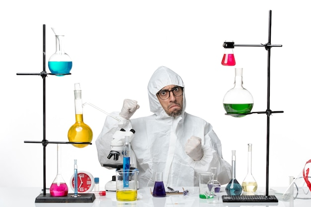 Vooraanzicht mannelijke wetenschapper in speciaal beschermend pak zittend en boos gevoel