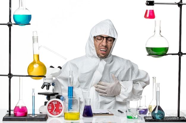 Vooraanzicht mannelijke wetenschapper in speciaal beschermend pak zittend met oplossingen met hartzeer