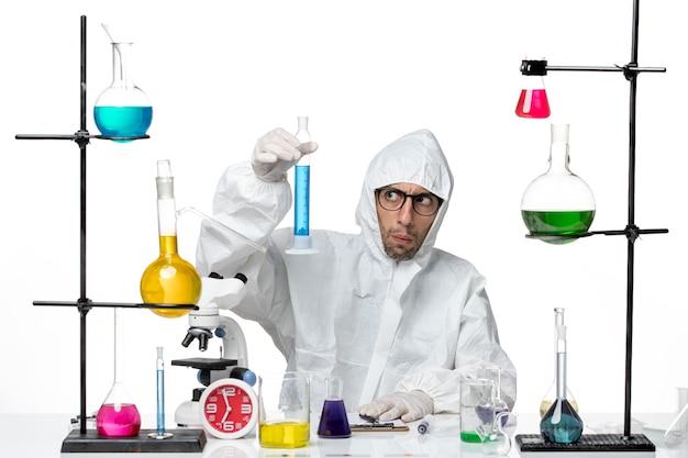 Vooraanzicht mannelijke wetenschapper in speciale beschermende pak houden kolf met blauwe oplossing