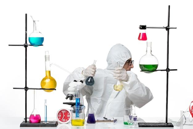 Vooraanzicht mannelijke wetenschapper in speciale beschermende pak kolven met oplossingen te houden
