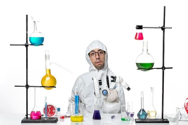 Vooraanzicht mannelijke wetenschapper in speciale beschermende pak met microscoop