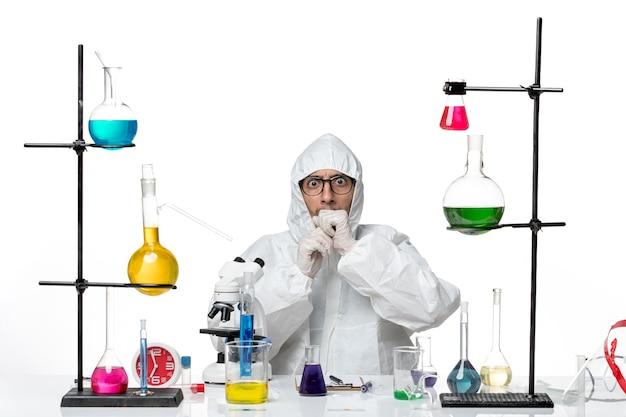 Vooraanzicht mannelijke wetenschapper in speciale beschermende pak zitten