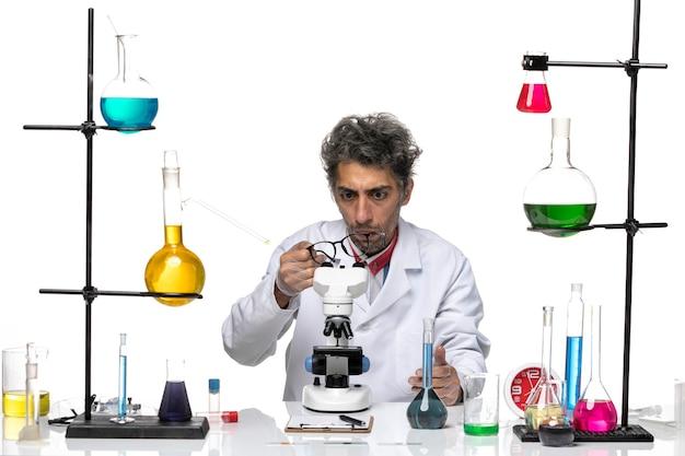 Vooraanzicht mannelijke wetenschapper in wit medisch pak die zijn zonnebril controleert