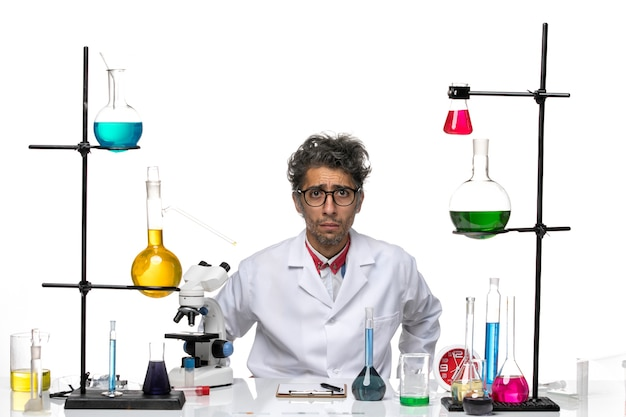 Vooraanzicht mannelijke wetenschapper in wit medisch pak verdrietig