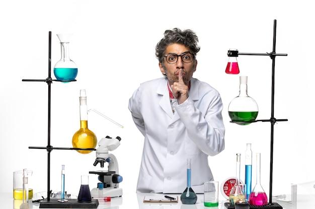 Vooraanzicht mannelijke wetenschapper in wit medisch pak vraagt stil te zijn